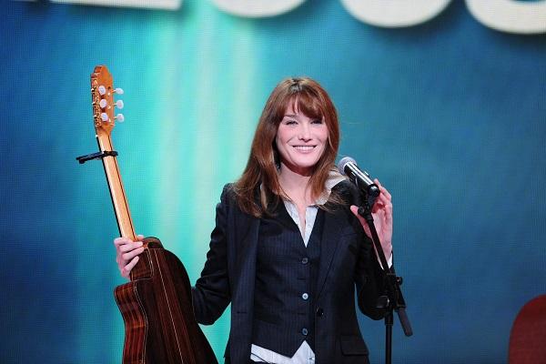 Carla Bruni debout, souriante, avec un guitare dans la main