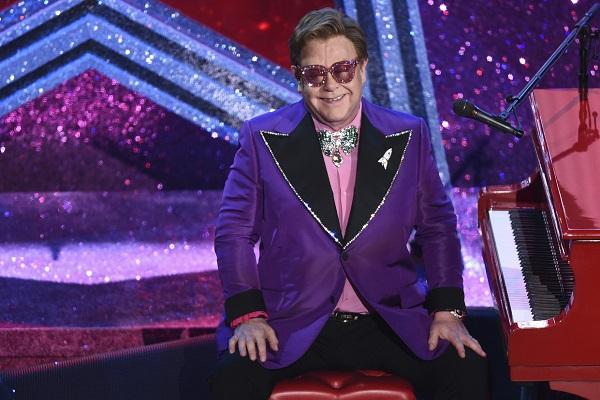 Elton John est assis devant son piano rouge