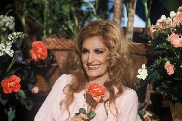 Dalida assise souriante entourée de fleurs